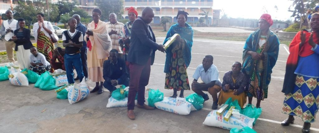 Members of Board of Directors and Mr. Sam Niyonzima, the District Community Development Officer, handing over food relief and other items to FOHU families.